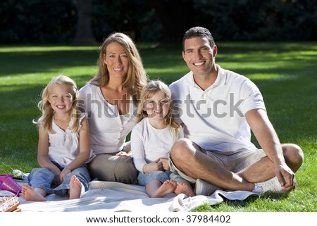 A young family with mother father and two blond daughters having a picnic in a sun bathed green park