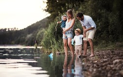 A young family with two toddler children outdoors by the river in summer.