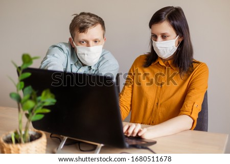 A young family works from home at the computer. Quarantined couple coronavirus in medical masks. The call to stay home safe. Order food products online. Laptop freelancer dispute business office