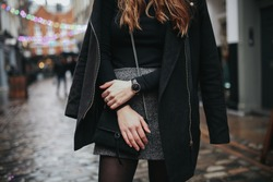 A young fashionable woman under rain wearing black top, black coat and grey skirt. Concept of street style, blogging and lifestyle. Horizontal image with selective focus on the details of the outfit.