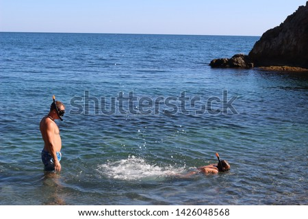 A young father and his daughter are having fun swimming in the black sea in an aqualung. Positive holidays with children in Crimea, Russia #1426048568