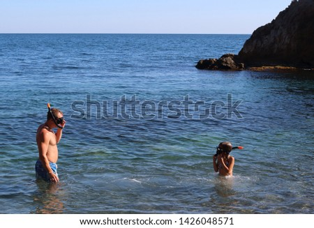 A young father and his daughter are having fun swimming in the black sea in an aqualung. Positive holidays with children in Crimea, Russia #1426048571