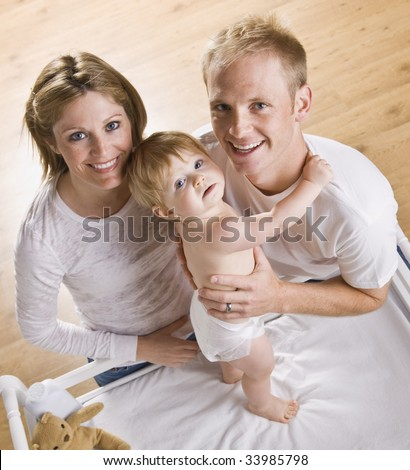 A young father and mother are holding their baby daughter on her changing table. They are looking up and smiling at the camera.  Square framed shot.