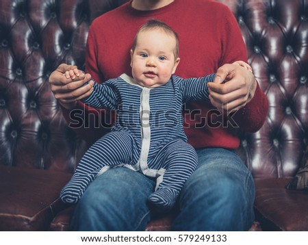 A young father is sitting on a sofa with his small baby