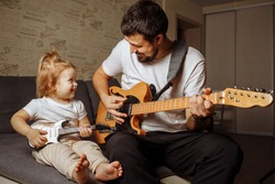 A young father teaches a little daughter to play the electric guitar while sitting on a sofa in an apartment during quarantine. Self-isolation at home.