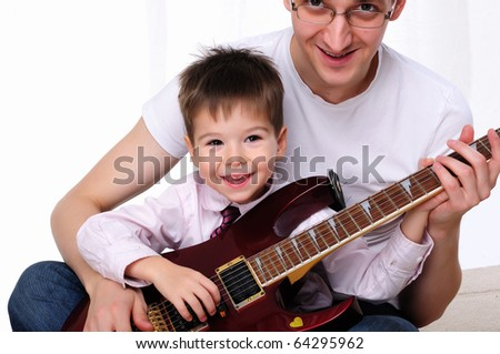 A young father teaches his young son to play guitar