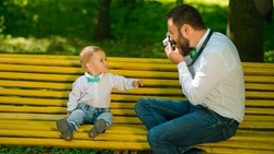 A young father with a beard sits on a yellow bench in the park and takes pictures of his young son. Father's Day.