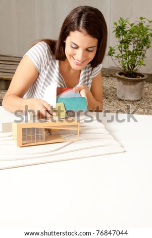 A young female architect testing a color swatch on a model house