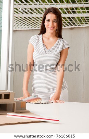 A young female architect with color swatches and a rough model