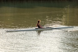 A young female athlete is rowing in a single scull on the Danube, Budapest Hungary