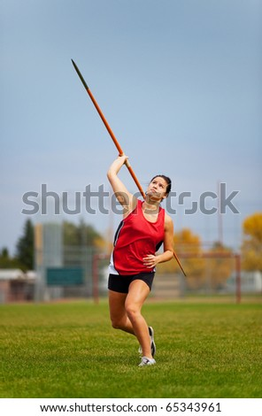 A young, female athlete throwing a javelin in a track and field event.