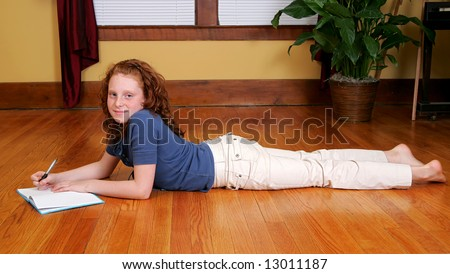 a young female child laying on the hardwood floor and writing in a journal or diary