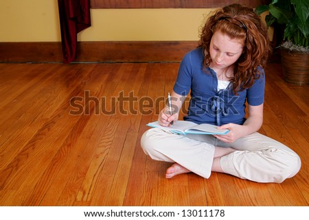 a young female child sitting on the hardwood floor and writing in a journal or diary