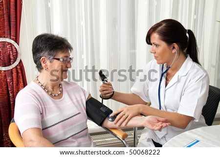 A young female doctor measuring patient blood pressure