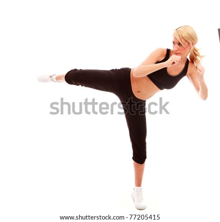 A young female dressed in black gym clothes performing a karate kick on isloated white background