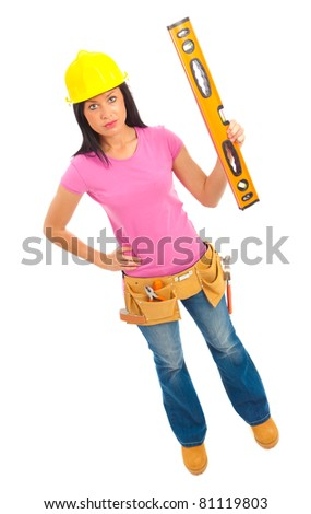 A young female dressed in blue jeans and pink top  and yellow hard hat holding a spirit level