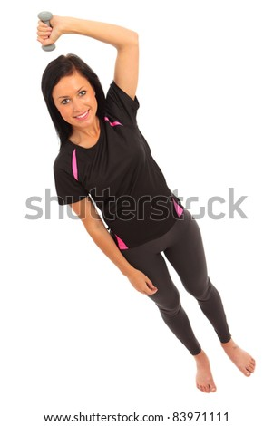 A young female dressed in gym clothes performing dumbell fly exercise on isolated white background - stock photo