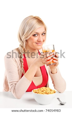 A young female drinking an orange juice and eating cornflakes at breakfast isolated on white background