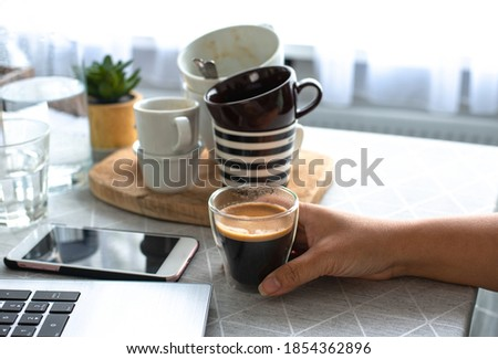 A young female freelancer  working from home holding a cup of coffee with many cups in the background drinks too much coffee caffeine addiction anxious and crazy in maniac bad lifestyle concept Сток-фото ©
