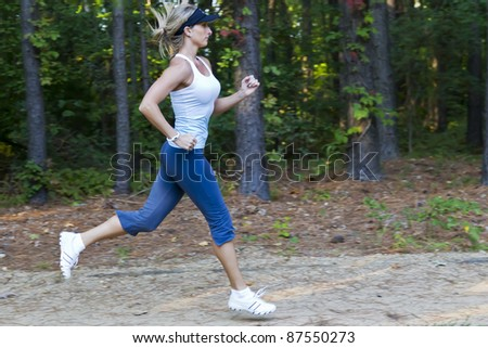 A young female jogger running through the woods