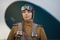 A young female pilot in uniform of Soviet Army pilots during the World War II. Military shirt and flight helmet and goggles. Photo in retro style.