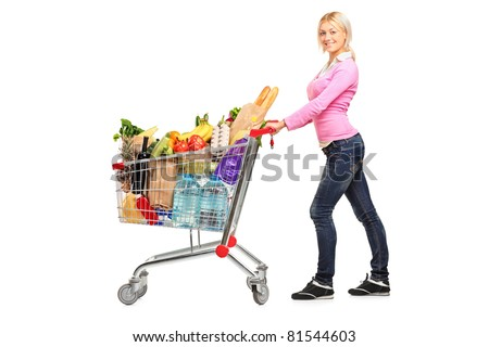 A young female pushing a shopping cart full with groceries isolated on white background