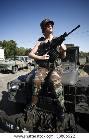 A young female soldier with an assault rifle.