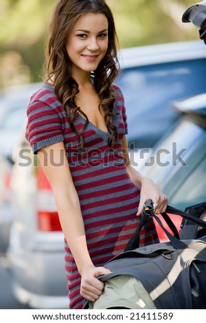 A young female student putting large bag into the car