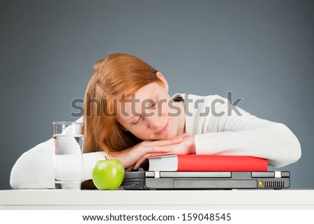 A young female student sleeping over a textbook and a notebook computer instead of studying.