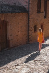 A young female tourist in a summer dress explores a country lane in the quaint and charming medieval French village of Conques, Aveyron Occitanie France.