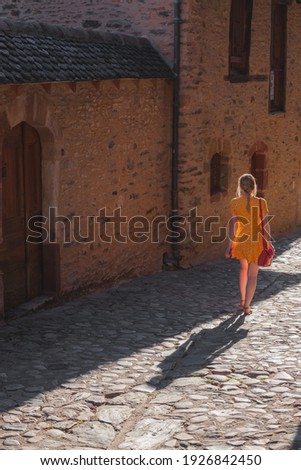 A young female tourist in a summer dress explores a country lane in the quaint and charming medieval French village of Conques, Aveyron Occitanie France. Photo stock ©