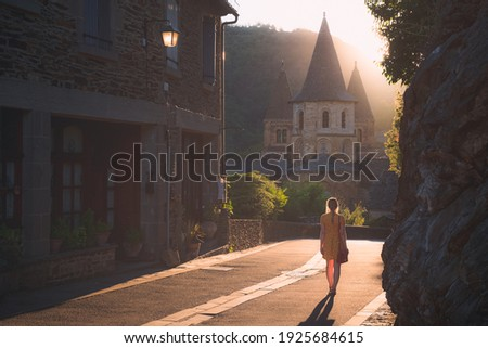 A young female tourist in a summer dress explores the quaint and charming medieval French village of Conques, Aveyron at sunset or sunrise in Occitanie France. Photo stock ©