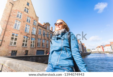 A young female tourist sits near the water and basks in the sun on Jan van Eyck Square in Bruges, Belgium. Travel in Belgium #1394074943