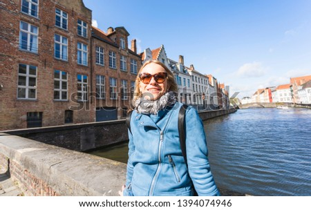 A young female tourist sits near the water and basks in the sun on Jan van Eyck Square in Bruges, Belgium. Travel in Belgium #1394074946