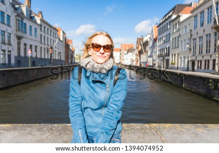 A young female tourist sits near the water and basks in the sun on Jan van Eyck Square in Bruges, Belgium. Travel in Belgium #1394074952