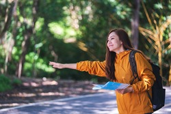 A young female traveler hitchhiking and stopping car with thumbs up on a mountains road