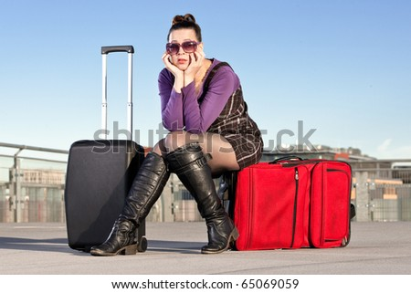 A young female traveler looking fed up and bored with her baggage in an airport terminal scenario
