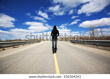 A young female walking down the middle of the road maybe lost in thought or not knowing where life will take her.