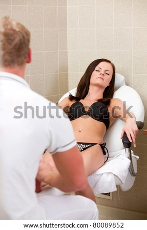 ... A young female wearing a bikini receiving a pedicure and foot massage in
