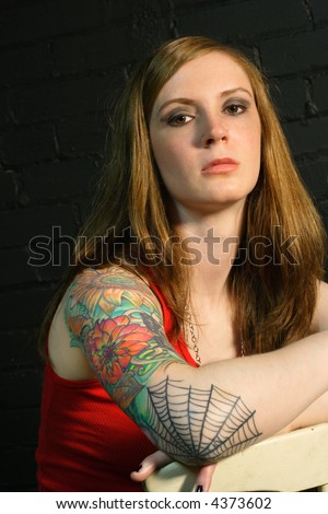 stock photo : A young female with serious stare and arm tattoo.