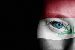A young female with the flag of Iraq painted on her face on her way to a sporting event to show her support.