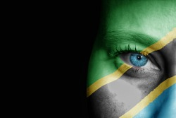 A young female with the flag of Tanzania painted on her face on her way to a sporting event to show her support.