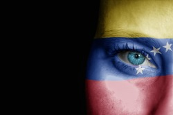A young female with the flag of Venezuela painted on her face on her way to a sporting event to show her support.