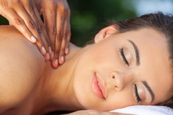 A young female woman or girl relaxing outside at a health spa while having a massage