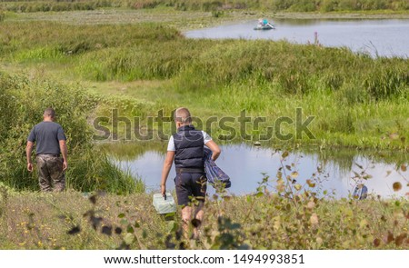 A young fisherman carries equipment to the boat, on a sunny day fishing in a freshwater pond for spinning and fishing rods, promises an excellent catch for outdoor enthusiasts in solitude with nature #1494993851