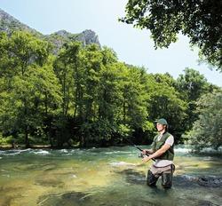 A young fisherman fishing on a riverTreska, Macedonia