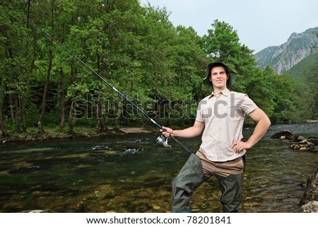 A young fisherman posing while fishing on a river with trees in the background