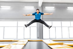 A young fit happy man jumping and flying on trampoline in fitness gym
