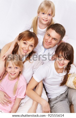 A young friendly family sitting and looking at camera