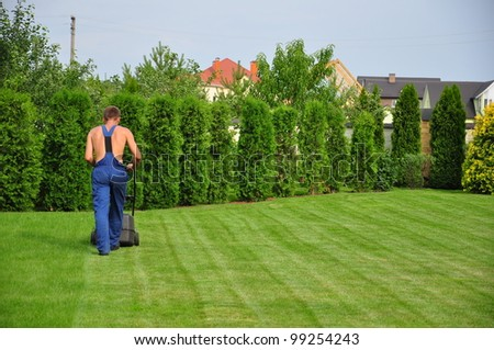 a young gardener cutting grass on garden